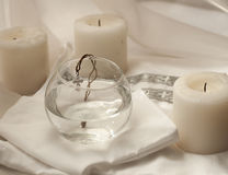 Ein Baumwolltauf- Hemd für ein neugeborenes Baby, Kerzen und ein Kreuz auf einer groben Schnur puttete in ein Glas Wasser Lizenzfreie Stockfotos
