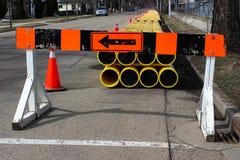 Ein Bausperrenzeichen mit Rohren auf der Straße Lizenzfreie Stockfotografie