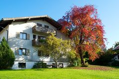 Ein bayerisches Haus im Herbstfarbenbaum Lizenzfreies Stockfoto