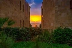 Ein beautifu und ein bunter Sonnenuntergang in Meer zwischen zwei Gebäuden und einem Garten Lizenzfreies Stockbild