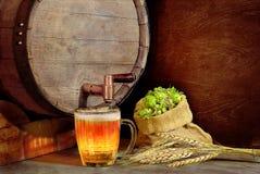 Ein Becher Bier auf dem Hintergrund von hölzernen Fässern, von Gerste und von h Stockfoto