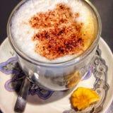 Ein Becher Cappuccino auf einem suacer Lizenzfreies Stockfoto