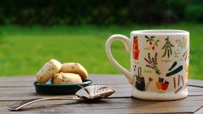 Ein Becher dampfiger grüner Tee auf einem rustikalen hölzernen Gartentisch im hinteren Garten Stockfoto