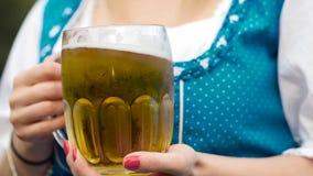 Ein Becher eines Bieres in einer Hand oktoberfest stock video footage