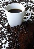 Ein Becher Kaffee umgeben durch Kaffeebohnen Lizenzfreie Stockfotografie