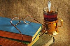 Ein Becher Tee, alte Bücher und Gläser auf Hintergrund des Jutefasers Lizenzfreie Stockfotos