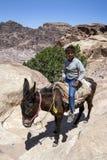 Ein beduinischer Junge reitet seinen Esel nahe dem hohen Ort des Opfers an PETRA in Jordanien Lizenzfreies Stockbild