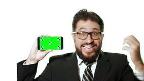 Ein Begriffsmodell Bärtiger Geschäftsmann mit den Gläsern, die einen Smartphone mit einem grünen Schirm halten stock video