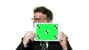 Ein Begriffsmodell Bärtiger Geschäftsmann mit den Gläsern, die eine Tablette mit einem grünen Schirm vor ihm halten stock footage