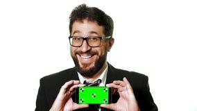 Ein Begriffsmodell Bärtiger Geschäftsmann mit den Gläsern, die einen Smartphone mit einem grünen Schirm als Visitenkarte halten stock video footage