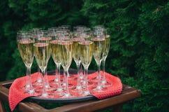 Ein Behälter mit einer roten Serviette und Champagner an einem Hochzeitsfest auf der Straße gegen den Hintergrund des Grüns stockbild