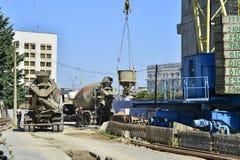 Ein Behälter flüssiger Beton steigt auf einer Höhe eines Kranes an einer Baustelle in Mogilev, Weißrussland im August 2017 stockbild