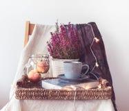 Ein Behälter mit einem Tasse Kaffee, Äpfel in einem Glas, helle Kette, Blumen und ein Schal stockfoto
