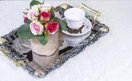 Ein Behälter mit einer weißen Schale und Blumen auf einem weißen Stoff stockbild