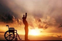 Ein behinderter Mann, der oben vom Rollstuhl steht Stockbild