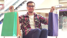 Ein behinderter Mann in einem Rollstuhl zeigt Einkaufstaschen und Lächeln an der Kamera Abschluss oben stock footage