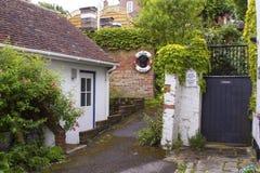 Ein belaubter Weg nahe dem Hafen in Lymington, Hampshire auf der Südküste von England mit Häuschen und von Gärten mit allen Arten Stockfotos