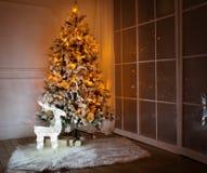 Ein beleuchteter Weihnachtsbaum mit Geschenken darunterliegend Stockfotos