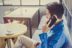 Ein Beratungspartner des Geschäftsmannes telefonisch beim Sitzen in der Kaffeestube stockbild