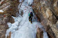Ein Bergsteiger, der auf Eis klettert lizenzfreie stockfotos