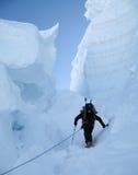 Ein Bergsteiger mit Skis in einer riesigen Gletscherspalte in den Alpen lizenzfreies stockfoto