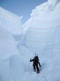 Ein Bergsteiger mit Skis in einer riesigen Gletscherspalte in den Alpen stockfoto