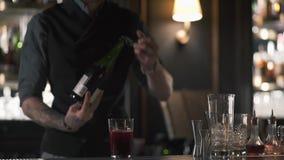 Ein Berufsbarmixer öffnet eine Flasche Champagner oder Sekt bei der Stellung am Barzähler in der Kneipe stock video footage