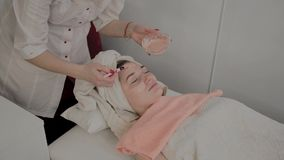 Ein Berufscosmetologist wendet eine Gesichtsmaske an einem jungen Mädchen mit einer Bürste an Neues Konzept im Cosmetology stock video
