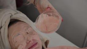 Ein Berufscosmetologist wendet eine Gesichtsmaske an einem jungen Mädchen mit einer Bürste an Neues Konzept im Cosmetology stock footage