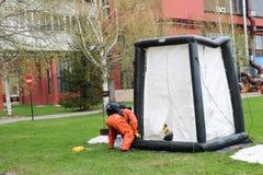 Ein Berufsfeuerwehrmann in einer orange speziellen feuerfesten Klage bereitet vor sich, ein weißes Sauerstoffzelt zu den Rettungs stockbild