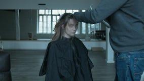 Ein Berufsfriseur arbeitet schnell und gut Ein Mann mit einem Stilisten macht eine Frisur für eine junge Schönheit stock video