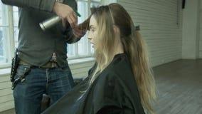 Ein Berufsfriseur macht eine Frisur für eine junge Frau am Standort Ein männlicher Stilist befeuchtet ihr Haar mit stock video