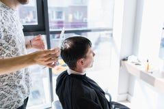 Ein Berufsherrenfriseur mit einem Kamm und Scheren in seiner Hand, die das nass schwarze und kurze Haar des Mannes in a anredet lizenzfreies stockfoto