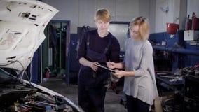 Ein Berufsmechaniker nimmt die Unterzeichnung vom Besucher der Autosorgfaltmitte für das Auto im Einsatz reparieren stock video footage