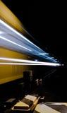 Ein beschleunigender gelber Zug nachts mit Kopien-Raum stockfotografie