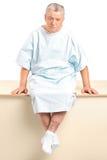 Ein besorgter älterer Patient, der in einem Krankenhaus sitzt Stockbilder