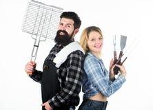 Ein besserer Grill für einen besseren Koch Glückliches Hippie- und sexi Mädchenholdingpicknick eingestellt für Grill Familienpaar lizenzfreies stockfoto
