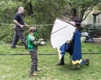 Ein Besucher, der in einem Rumpfkostüm gekleidet wird, kämpft mit einem Ritter im Ring am Purim-Festival mit König Arthur in der  lizenzfreie stockfotografie