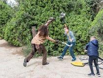 Ein Besucher kämpft mit einem Festivalteilnehmer, der als Barbar mit Plastikwaffen am Purim-Festival mit König Arthur herein gekl lizenzfreies stockbild