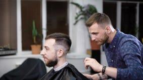 Ein Besucher zum Friseursalon kam, eine stilvolle Frisur im Friseursalon zu erhalten, ein erwachsener Mann erwartet das Haar getr stock video footage