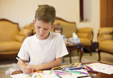 Ein Junge mit Liste des Papiers und der Filzstifte Lizenzfreie Stockfotografie