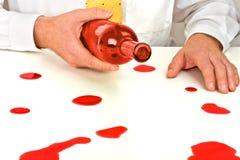 Ein betrunkener Mann, der sehr unkoordiniert schauen und bleary gemustert, eine Flasche Wein anhalten Lizenzfreie Stockbilder