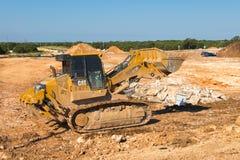 Ein beweglicher Schmutz und ein Felsen des gelben Bahnladers Caterpillars 973D Stockfoto