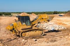 Ein beweglicher Schmutz und ein Felsen des gelben Bahnladers Caterpillars 973D Stockfotografie