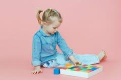 Ein bezauberndes kleines Mädchen in der Denimkleidung liegt auf einem rosa Hintergrund unter hölzernen farbigen Würfeln und dem L stockfotos