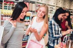 Ein Bild des blonden Mädchens Stück Kosmetik in ihren Händen halten Asiatisches Mädchen hält Rohr der Creme und schaut zu lizenzfreie stockfotos