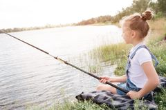 Ein Bild des Mädchens allein sitzend am Flussufer Sie fischt Mädchen hält Fischstange mit beiden Händen Sie schaut stockfotos