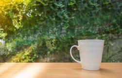 Ein Bild des selektiven Fokus eines Tasse Kaffees auf Holztisch im grünen Garten Stockbilder