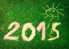 Ein Bild des Textes 2015 und der lustigen Sonne auf einer grünen Wand Lizenzfreie Stockfotos
