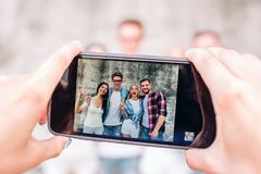 Ein Bild menschlichen ` s übergibt das Halten des Telefons Dieser Mensch macht Foto von vier glücklichen Menschen Sie stehen auf  Lizenzfreies Stockfoto